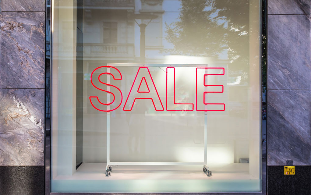 glass window of a store with SALE in bold red, outlined letters