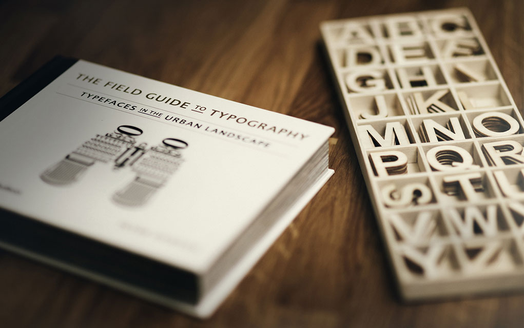 The field guide to typography book and wooden letters on a desk