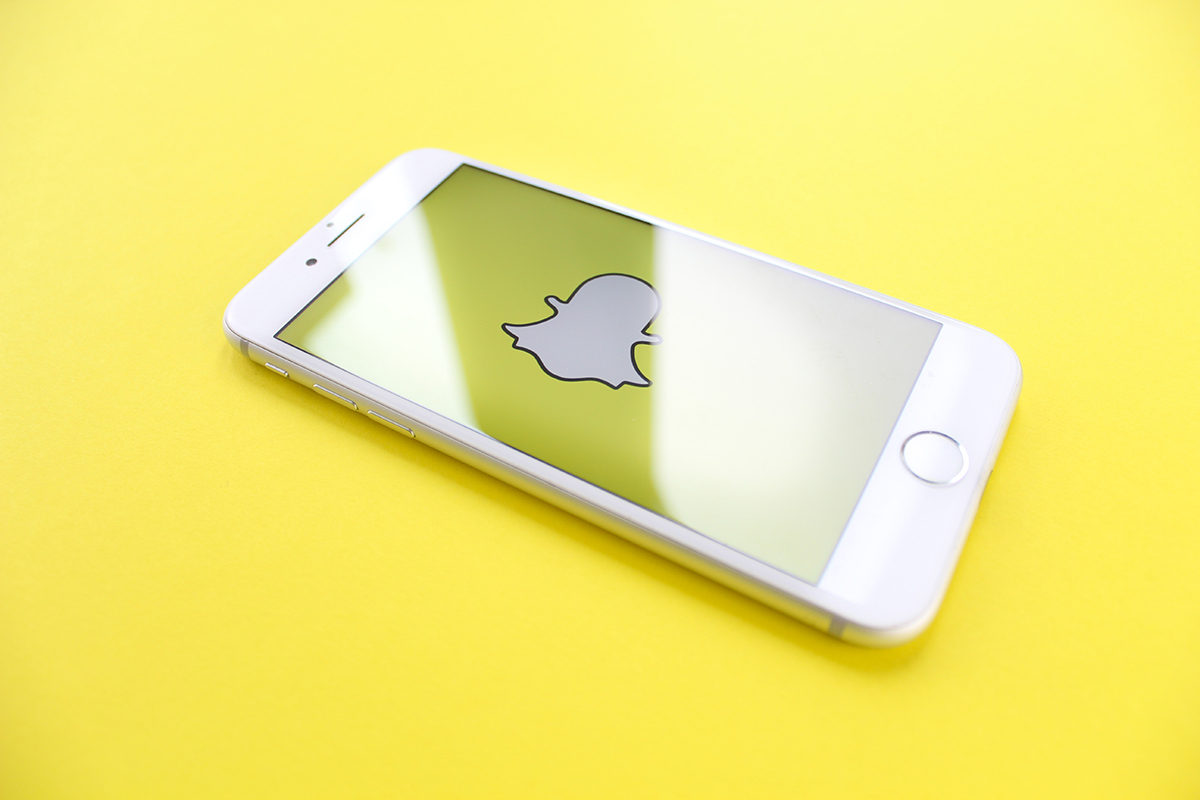 Snapcat logo on a phone with yellow brand color